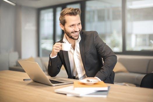 Мужчина с кофе за ноутбуком